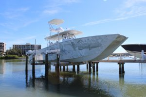 A boat lift suspended between eight pilings holds a large boat in Palm Bay, FL.
